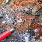Cross-cutting quartz carbonate bonanza coarse gold and multi-kilos silver vein in outcrop within the south zone. Telluride minerals are suspected. Numerous bonanza precious metal and MS float boulders have been exposed with glacial ice melt back.